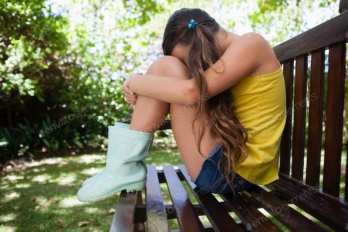 Seitenansicht der verärgerten Mädchen sitzt auf Holzbank