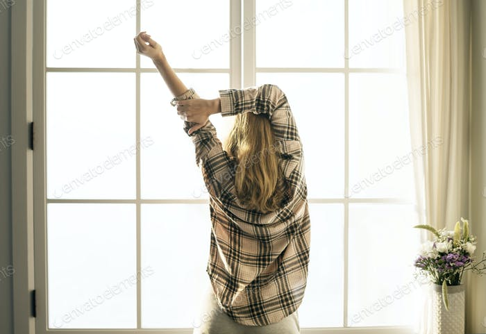 Rear view of woman stretching her arms in the morning