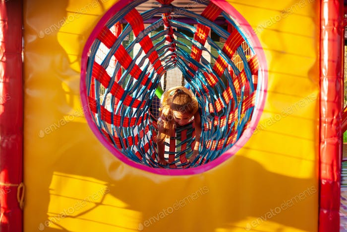 Little cute girl climbs through a bright long tunnel enjoying summer vacation