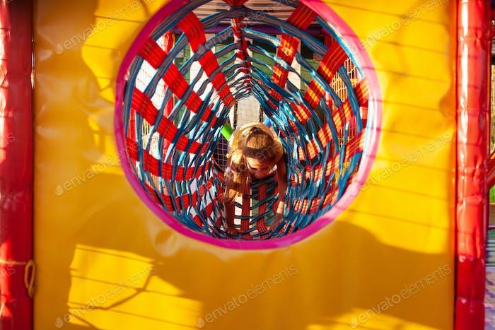 Kleines süßes Mädchen klettert durch einen hellen langen Tunnel und genießt Sommerferien