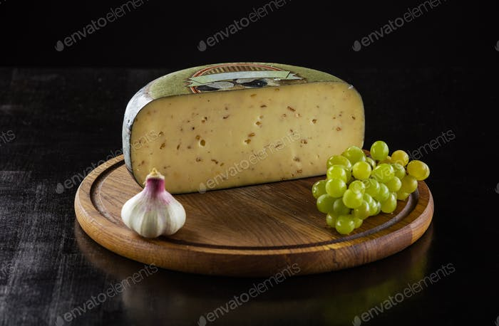 Piece of cheese with truffle, garlic clove and grapes on wooden