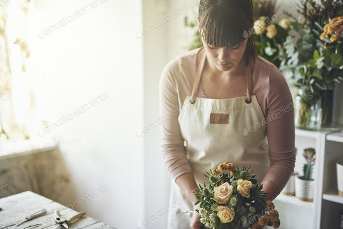 Florist working in her flower shop making a floral arrangement