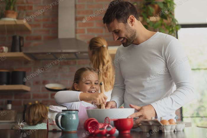 Happy Caucasian father and daughter preparing cookie on worktop in kitchen