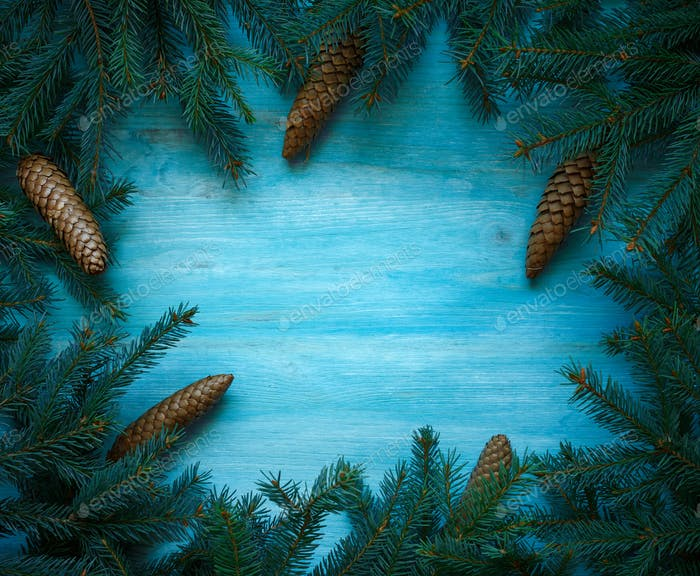 Christmas tree branches with cones on blue wooden texture ready