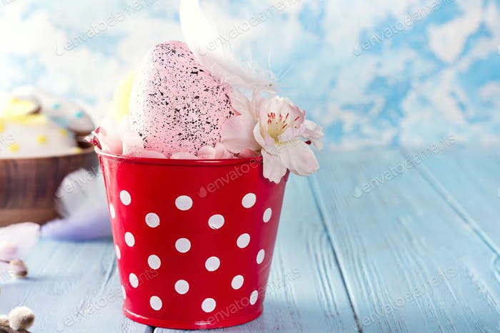 Easter basket (bucket) like nest with cute pink egg and flowers on blue wooden background. Copy