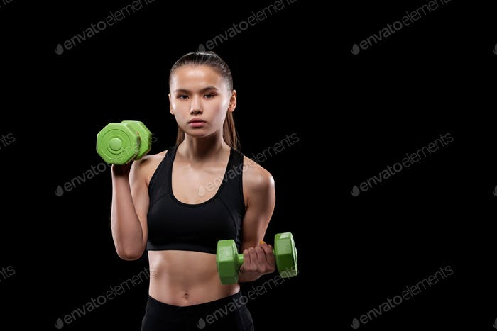 Pretty fit girl in black activewear holding green dumbbells while exercising