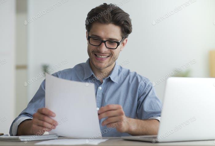 Happy Entrepreneur Lesen Finanzbericht sitzen am Laptop