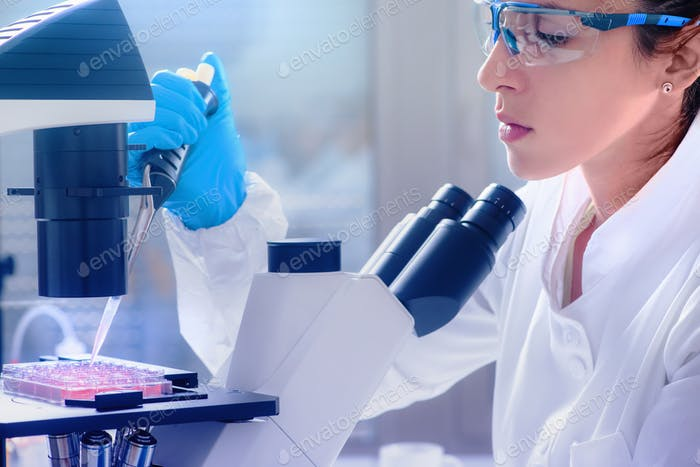 Female scientist with microscope in lab