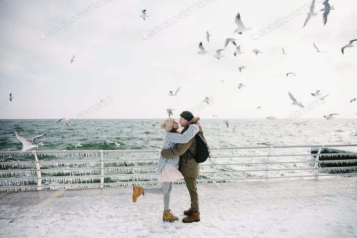 Young Couple Posing on Winter Quay at Sea With Seagulls