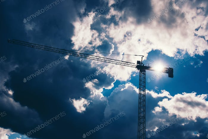 Silhouette of industrial construction crane with dramatic sky background. Details of industry