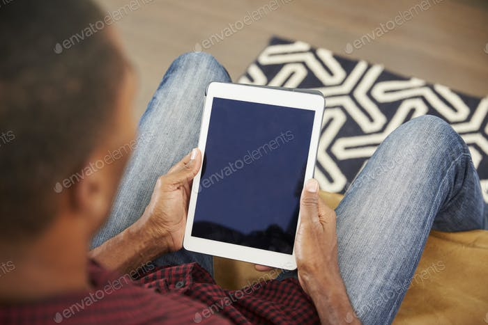 Man Sitting On Sofa At Home Looking At Digital Tablet