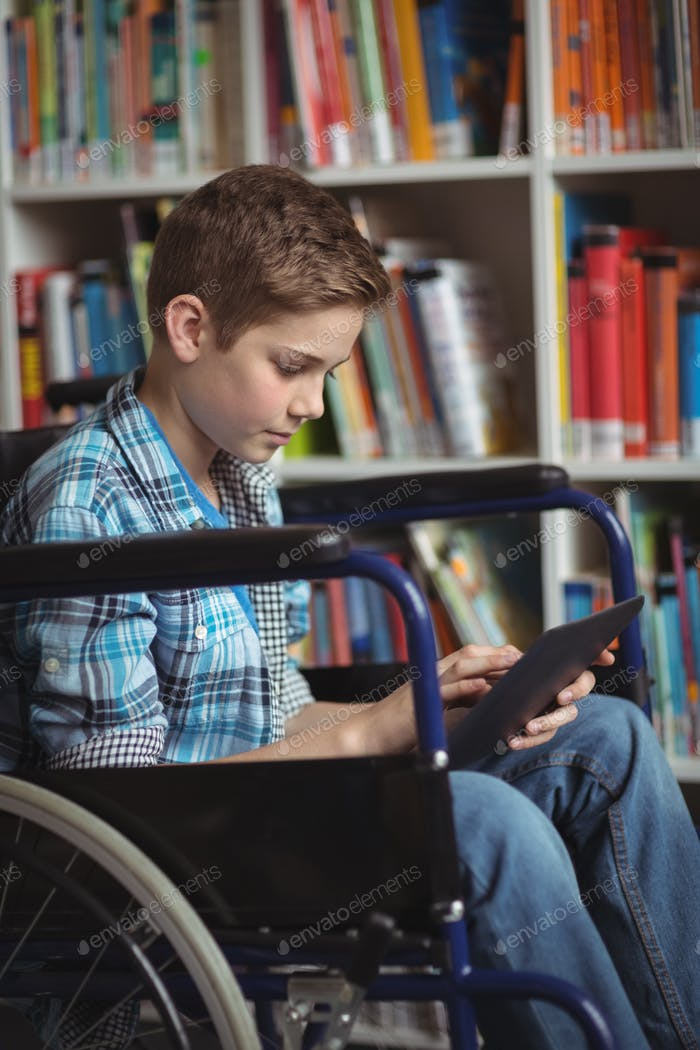 Disabled schoolboy using digital tablet in library