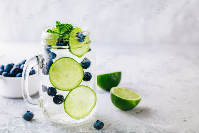 Infused detox water with green lime slices and blueberry.