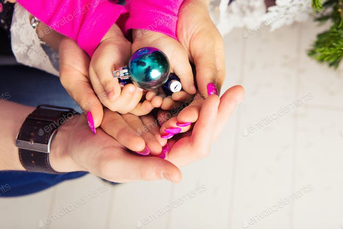 Christmas ball in the hands of the child and father, mother