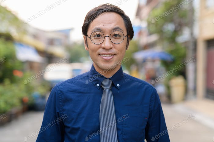 Face of Japanese businessman with eyeglasses outdoors