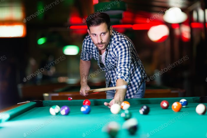 Hansome man playing pool in bar alone