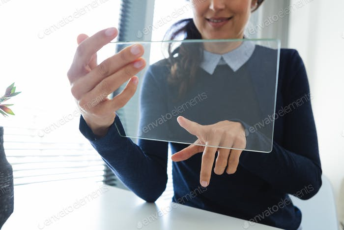 Mid section of female executive using glass digital tablet at desk