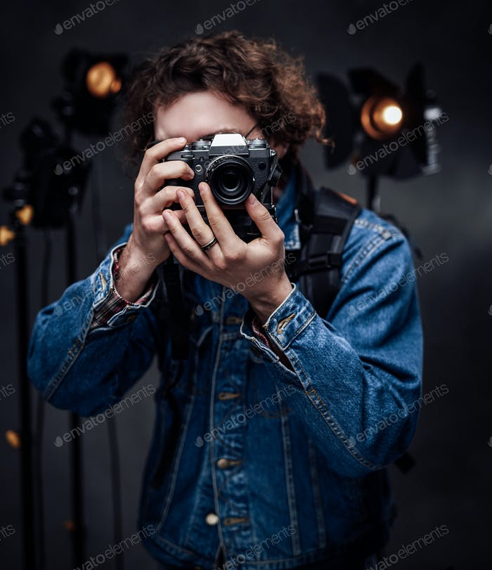 Handsome curly guy in glasses taking picture with digital camera in studio with lighting equipment