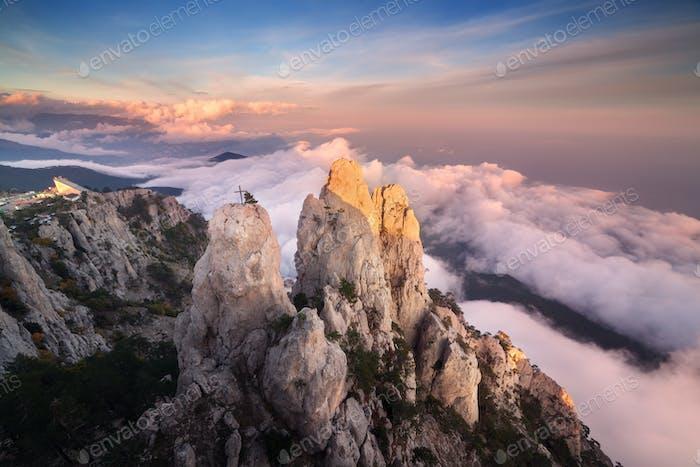 Berglandschaft. Hohe Felsen mit niedrigen Wolken bei Sonnenuntergang