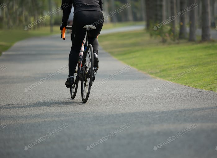 Woman cycling in tropical forest
