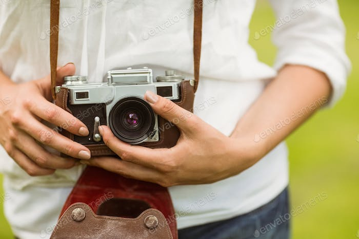 Mid section of woman holding vintage camera in the park