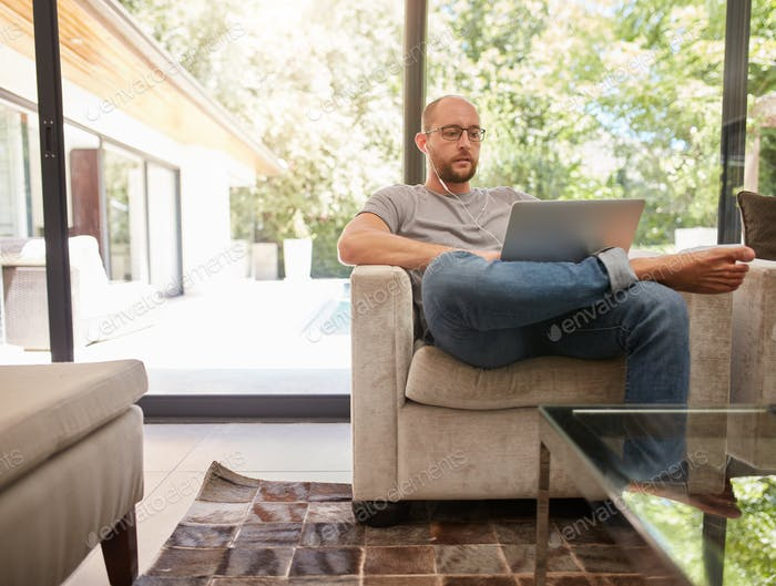 Relaxed man working on laptop at home