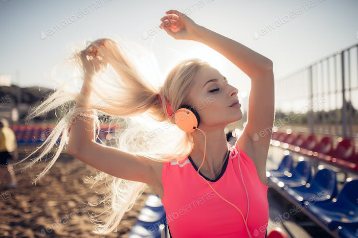 sport outdoor photo of beautiful young blonde woman in pink colorful suit listening to music on