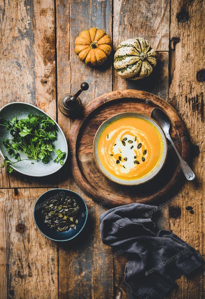 Kürbissuppe mit Samen, frischer Petersilie und Sahne in Schüssel