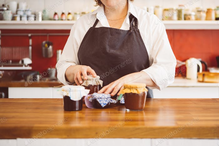 Woman at counter with jams and honey