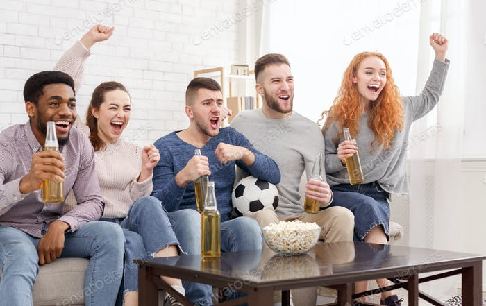 Happy football fans watching match on tv and celebrating victory