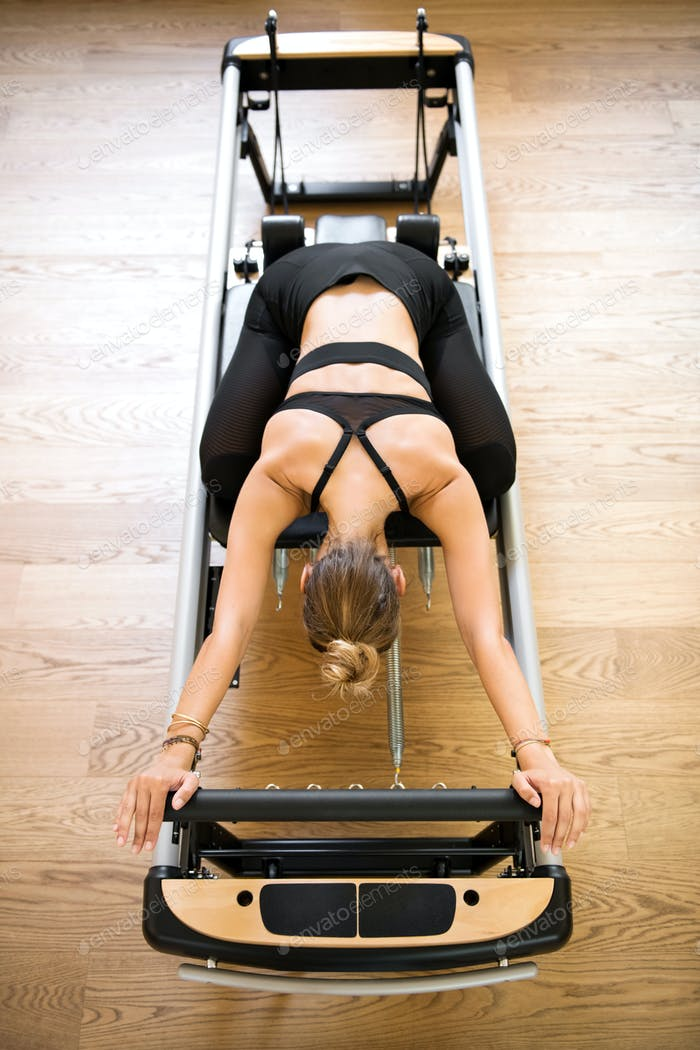 Woman doing pilates stretch on reformer bed