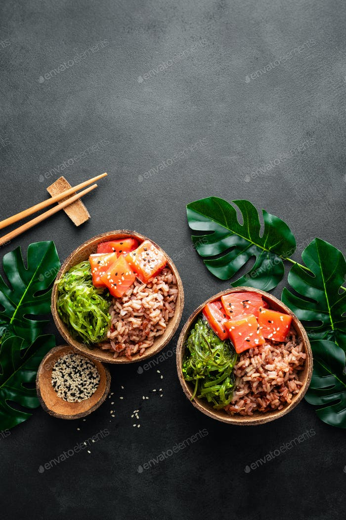 Poke bowl with raw salmon fish, chuka salad and rice in coconut bowls on black background