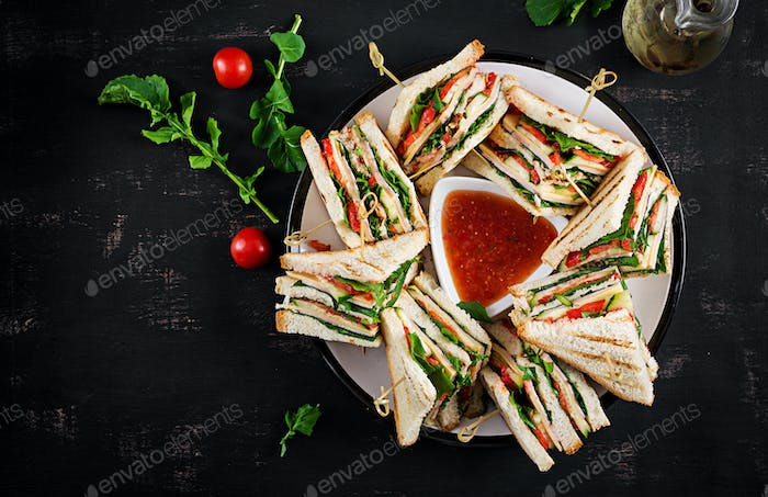 Club sandwich with ham, tomato, cucumber, cheese,  and arugula o