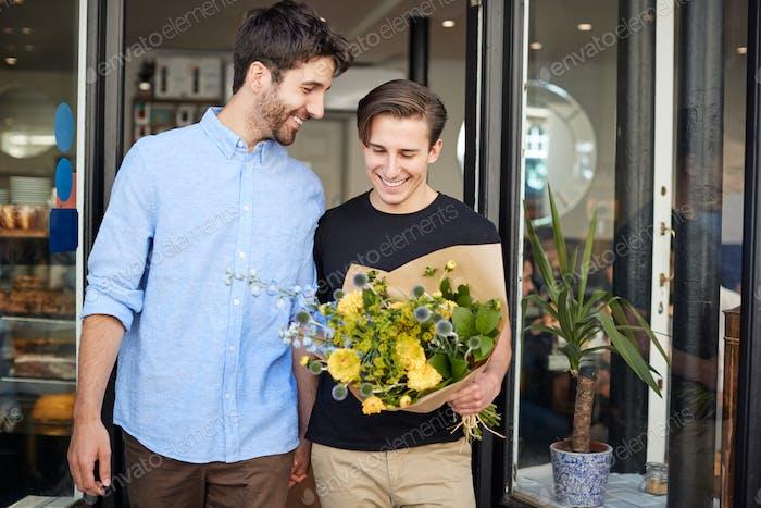Liebevolle männliche Homosexuell Paar halten Hände kommen aus Floristen halten Bündel von Blumen