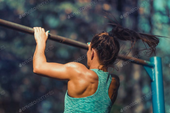 Woman Exercising on Horizontal Bar Outdoors in The Fall