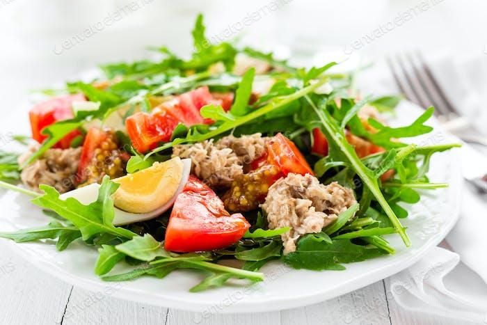 Salat mit Thunfisch. Gemüsesalat mit gekochtem Ei, Thunfisch und Rucola. Fischsalat