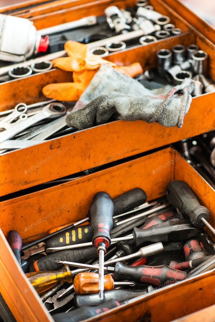 Open orange metal tool box with assorted tools