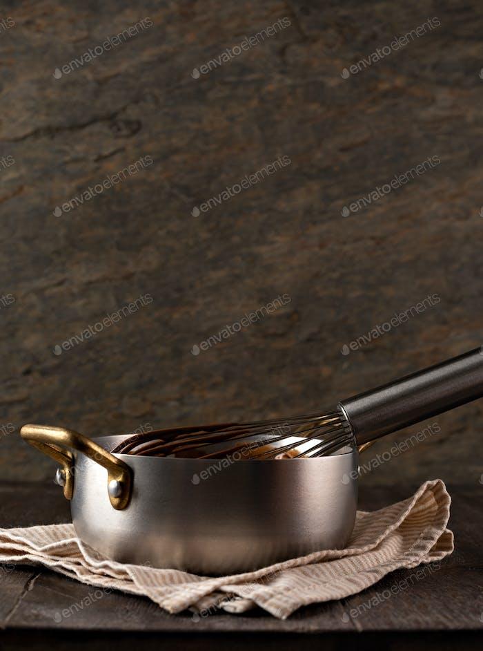 Flüssige Schokoladencreme aus einem Schneebesen in eine Schöpfkelle gießen.