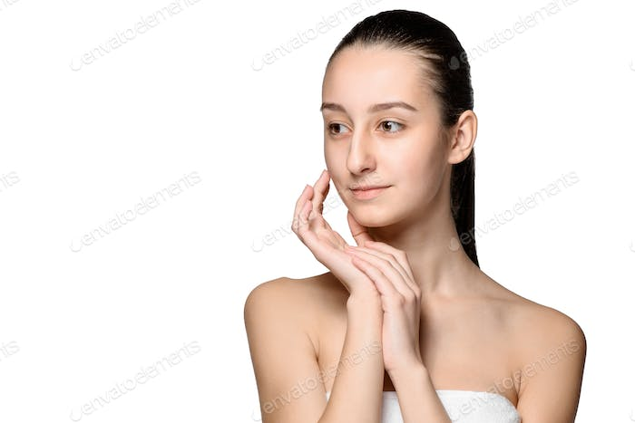 Portrait of beautiful girl stroking her face with healthy skin