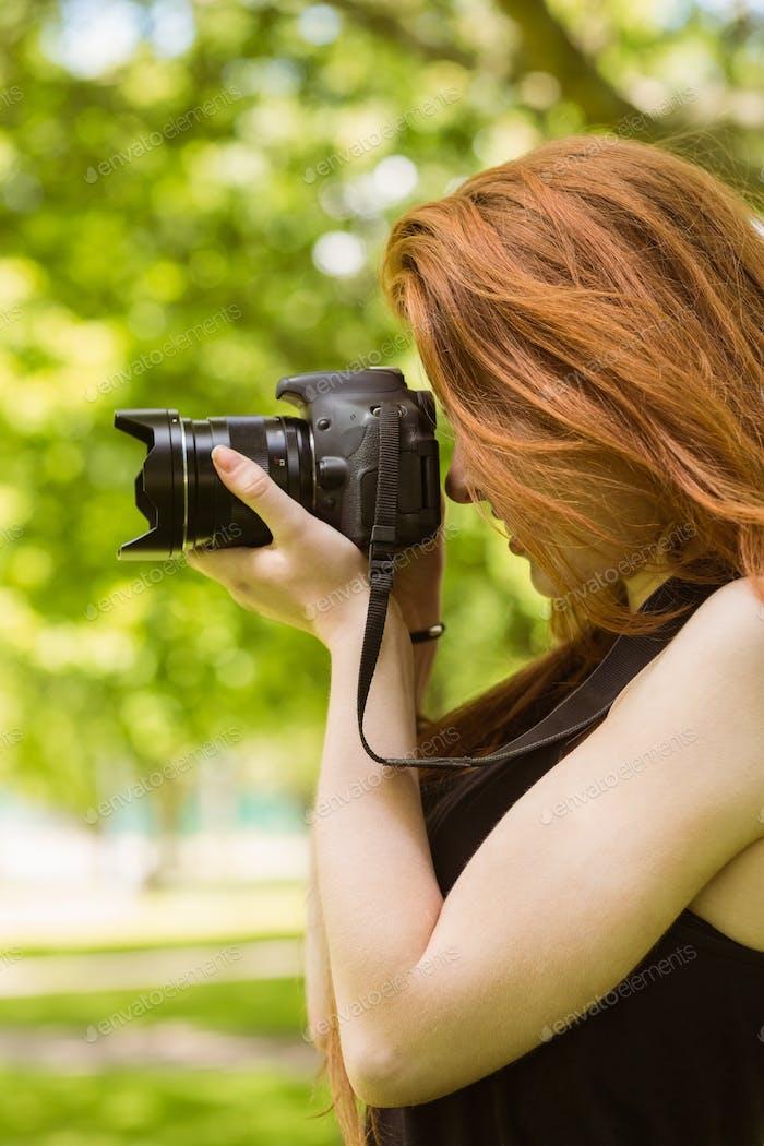 Seitenansicht der schönen weiblichen Fotografin im Park