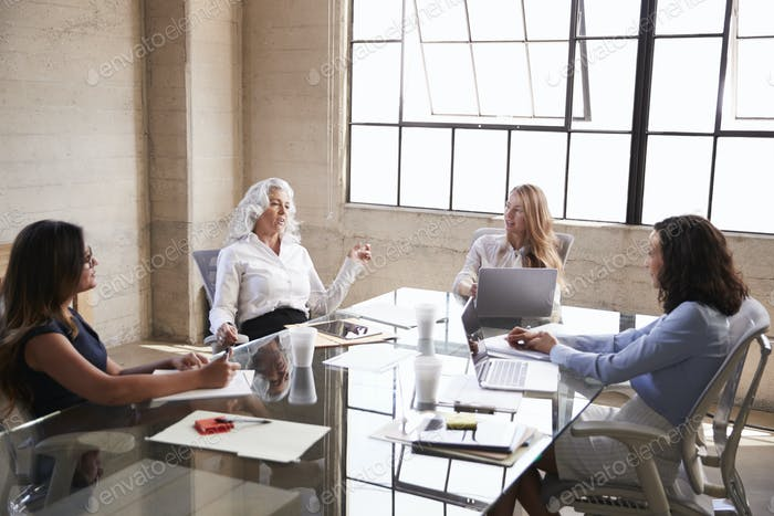 Four businesswomen in discussion in a meeting room
