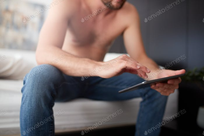 Young man sitting on the bed using digital tablet