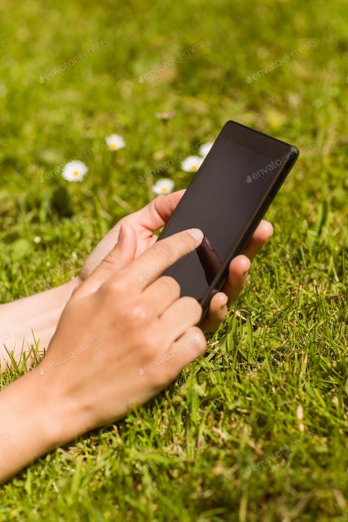 Nahaufnahme von ein ziemlich rothaarige halten Ihr Handy auf Gras