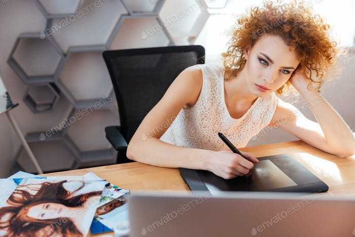 Concentrated woman photographer processing pictures using graphic tablet in office