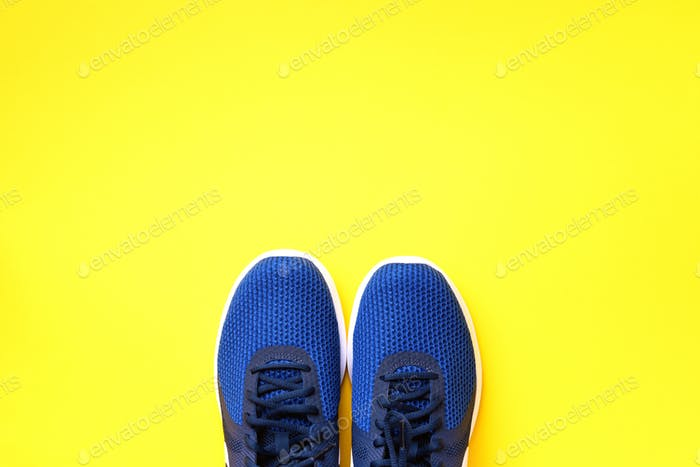 Pair of blue sport shoes on yellow background. Top view, copy space. Fitness, running and sport