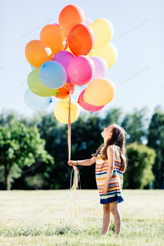 Little girl holding a bunch of colorful balloons in the park.