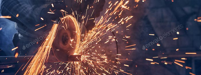 Man in special suit polishing metal with angle grinder