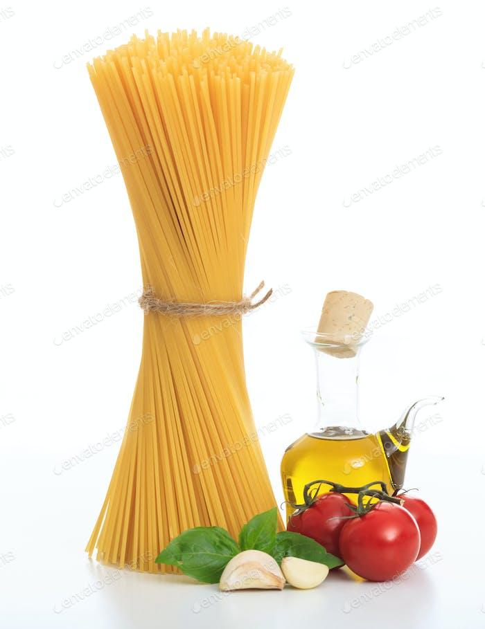 Italian cuisine concept. Raw spaghetti pasta, basil, tomatoes, olive oil and garlic