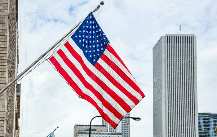 American flag in Chicago, Illinois downtown. Highrise buildings and cloudy sky background.