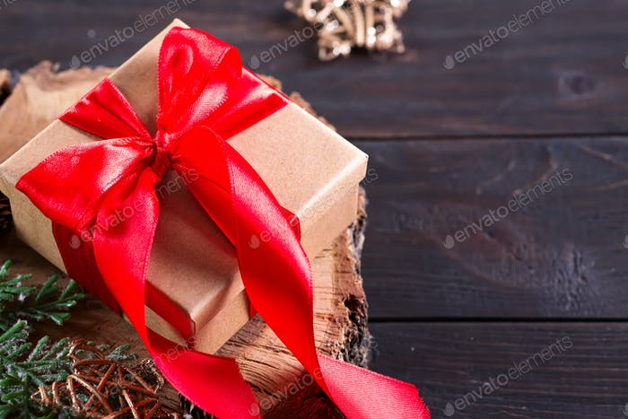 Brown gift box with red bow, christmas decoration on a wood cutting board on dark wooden background